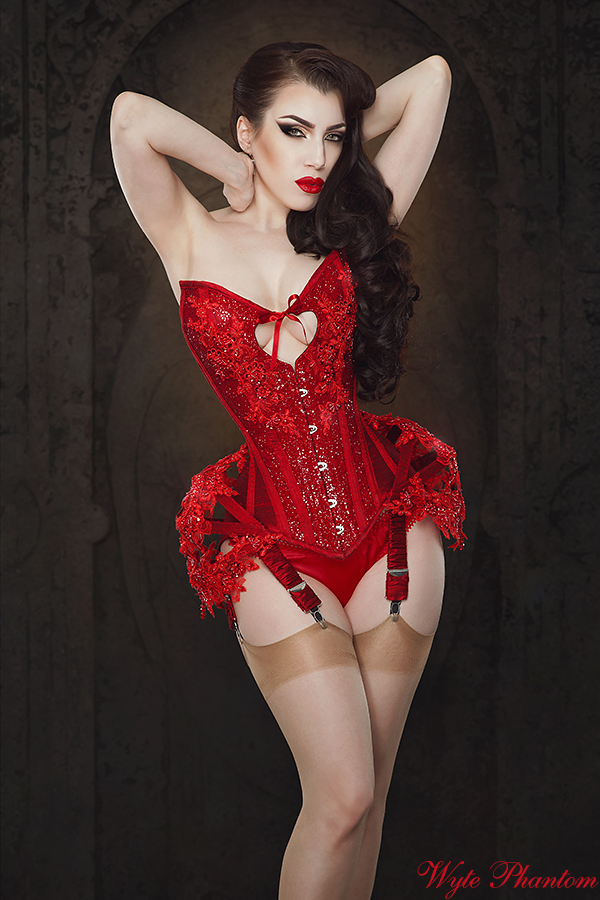 Threnody in Velvet/Iberian Black Arts for Wyte Phanton. Lingerie Trends - Corsetry. Red corset with sweetheart neckline and heart cutaway at bust with red garters and fawn stockings.