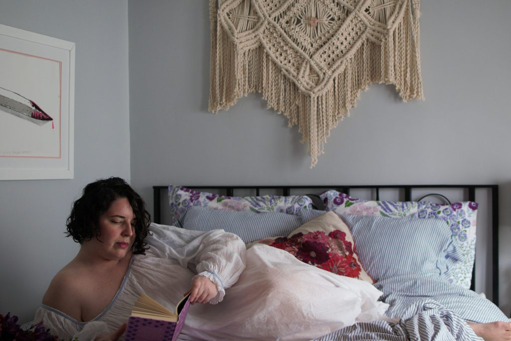 Model wearing handmade, sheer, intimate apparel laying in bed, reading a book, after a hysterectomy.