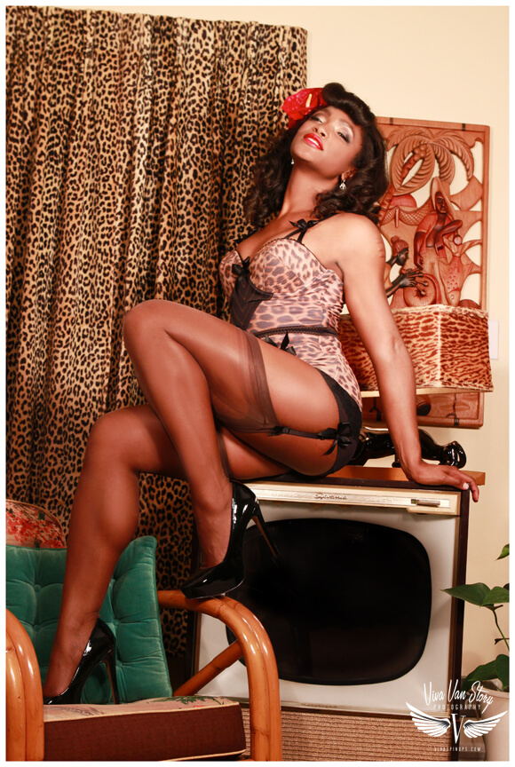 Black pinup Cora Harrington in leopard print vintage retro lingerie and stockings