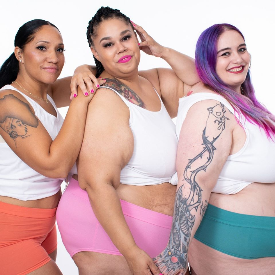 Three models wearing Kate and Vos Classics line. From left to right: pink boxers, light pink briefs, and green thongs.