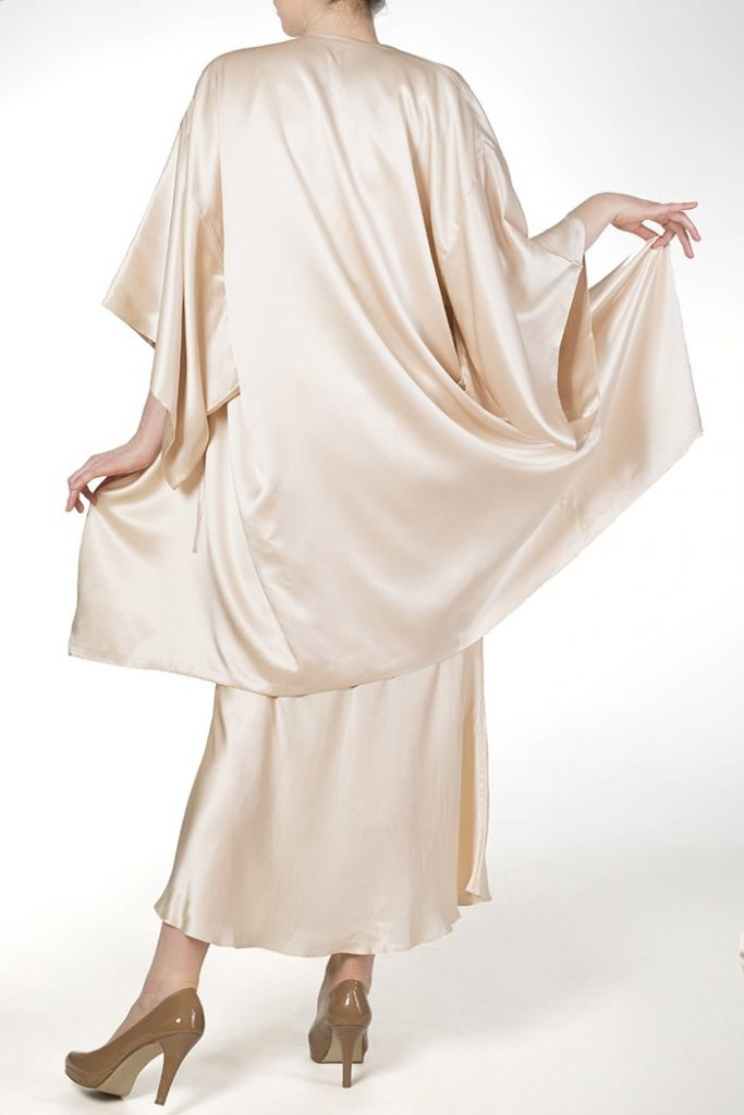 Model faces away from camera wearing ivory robe and long nightgown made of real silk