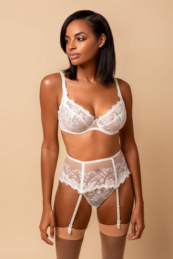Valentine's Day Lingerie. Model standing in front of blank background wearing white bra, garter belt, and knicker set with peach toned stockings.