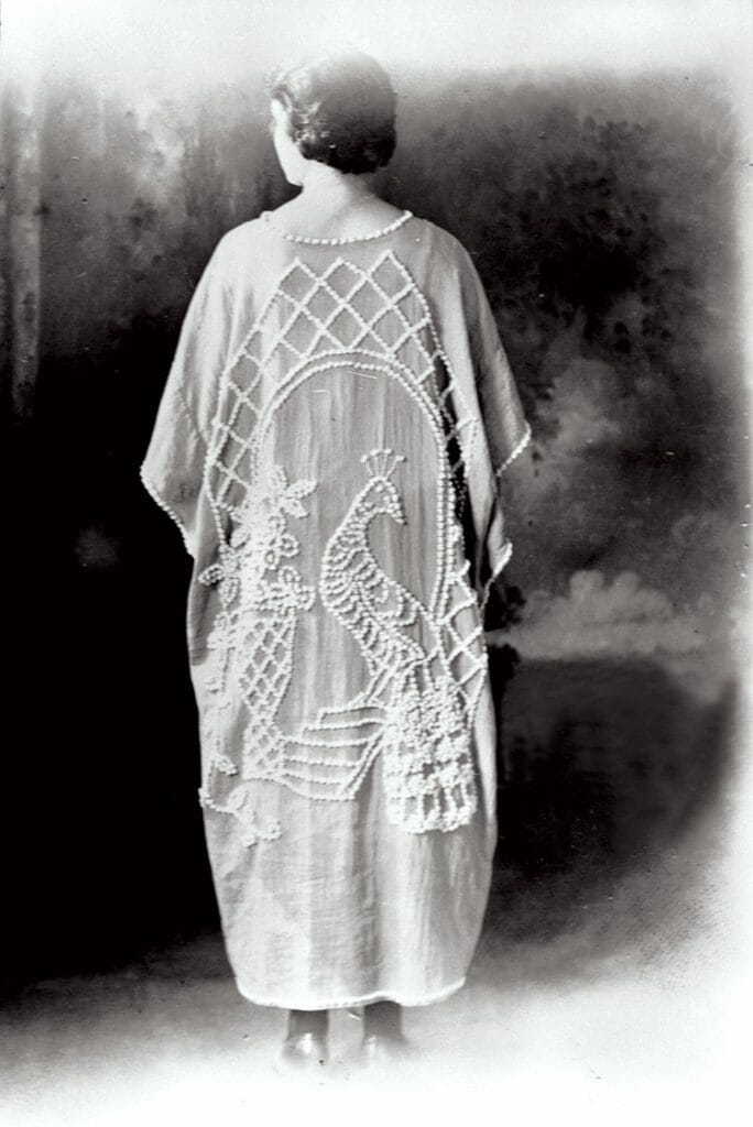 Mrs. Ralph Haney wearing a candlewick kimono with a peacock design, ca. 1920.