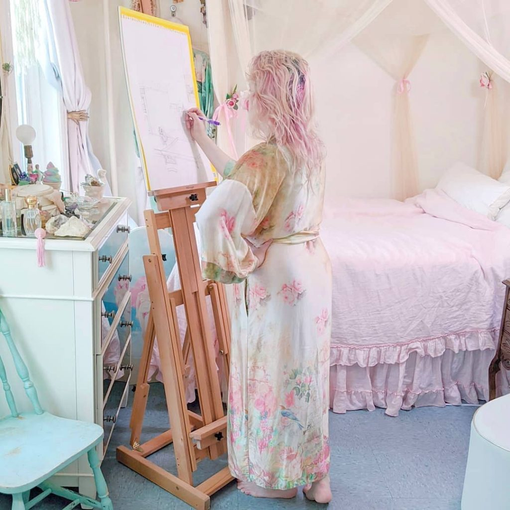 An example of silk lingerie you can use our oil removal technique on. Photo is of a woman with pink hair standing and drawing in front of easel in her bedroom. The bed has pink sheets, there's a mint green chair, and the dresser has perfume bottles and other accessories. The woman wears a light colored floral silk robe, yellow background with pink flowers and blue birds.