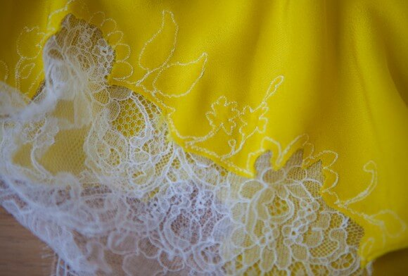 Interior view of machine-stitched lace appliqué on a Carine Gilson garment. Photography by K Laskowska