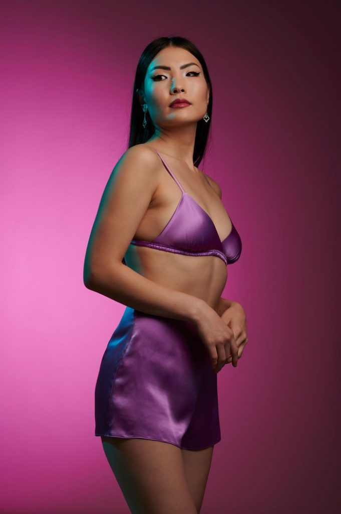 Model wears purple triangle bralette and tap shorts made of real silk by Angela Friedman
