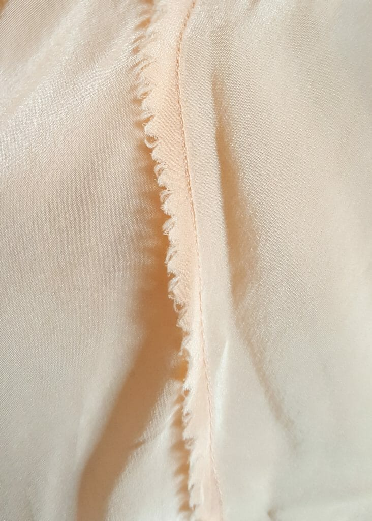 It is very rare to see a raw seam in contemporary lingerie, as it is time consuming and difficult to construct in a secure way. This 1930s teddy is sewn with raw seams that have been pinked (trimmed with zigzag toothed scissors to prevent fabric fraying) and finely topstitched (folded down and secured with an additional lockstitch, in this instance with a small stitch length). In contemporary manufacturing, it is much quicker to simply overlock this kind of seam. Photo by K Laskowska