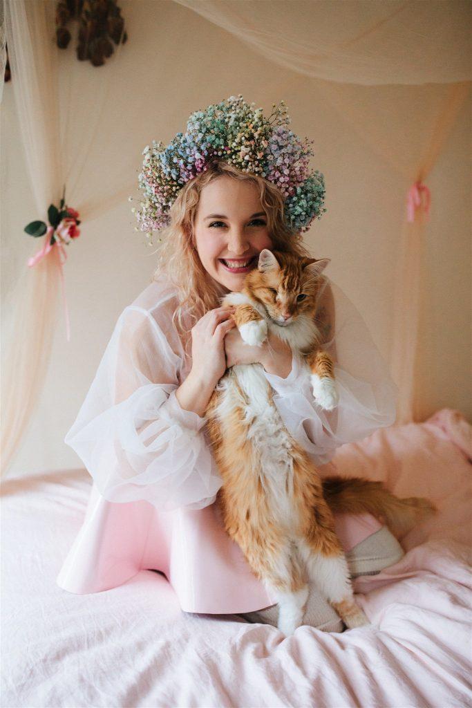Model kneeling, holing cat named Max.