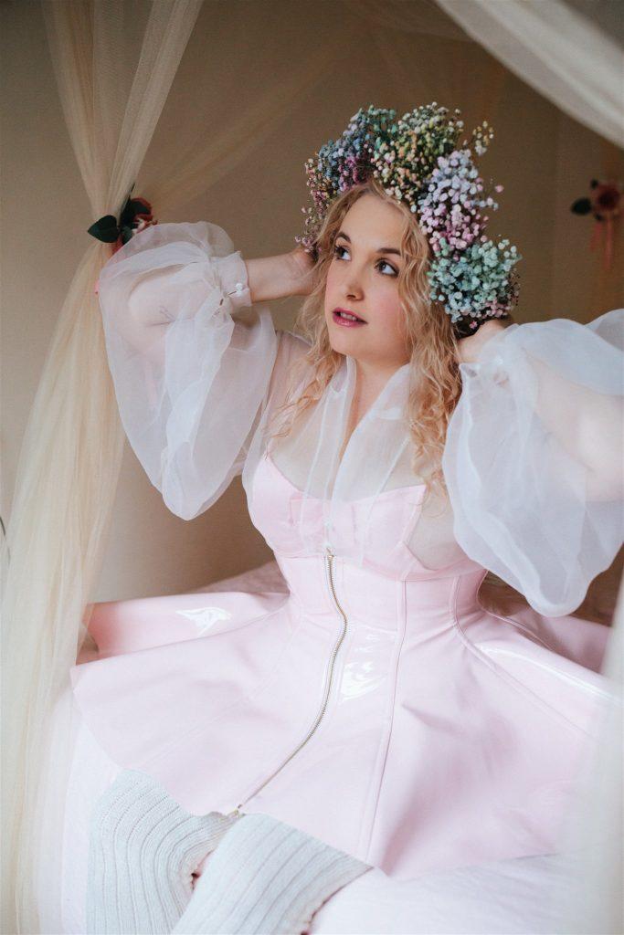 Model sitting wearing Artifice light pink PVC corset skirt.
