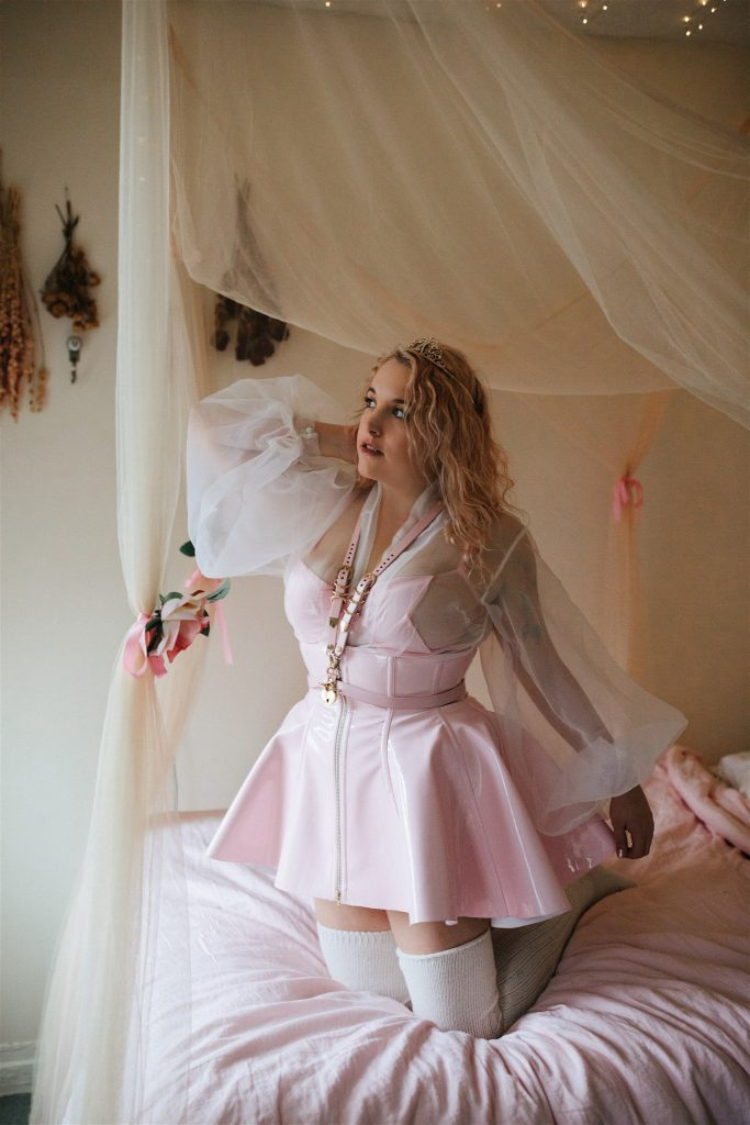 Alternate view of first model kneeling in Artifice light pink PVC corset skirt.