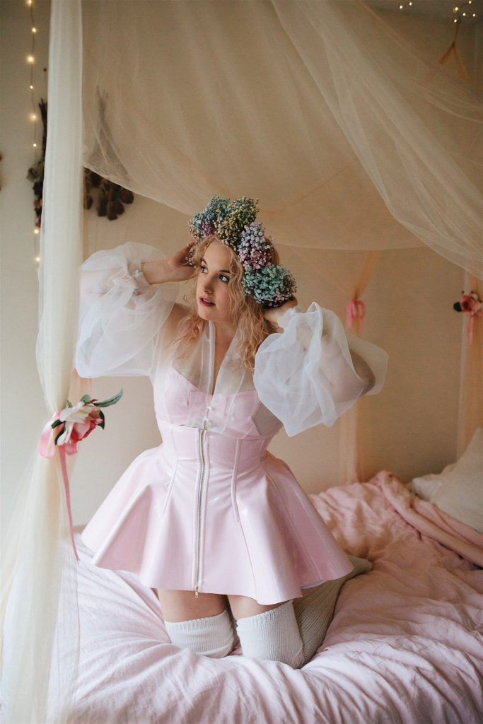 Model kneeling in bed, wearing light pink Artifice custom made PVC corset skirt with high waist and front zipper.