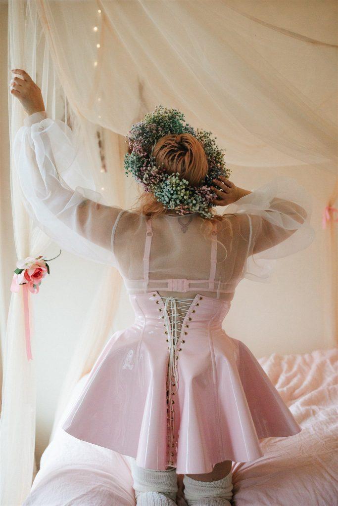 Back view of kneeling model wearing Artifice light pink PVC corset skirt.