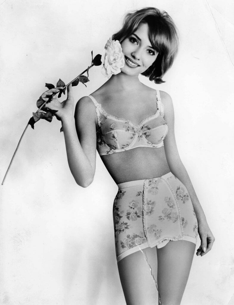 Vintage Aubade Lingerie Advertisement featuring a floral bra and girdle with the model holding a rose.