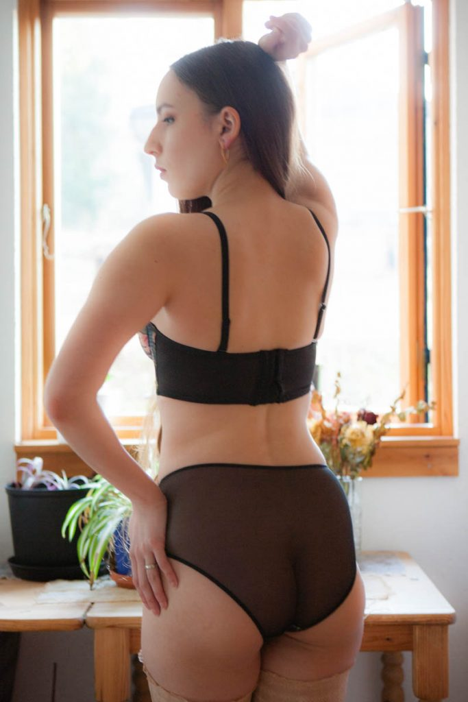 Back profile of model wearing Department Of Curiosities Longline Brassiere & High Waisted Briefs. Sheer, mesh, brief backing and bra wings.