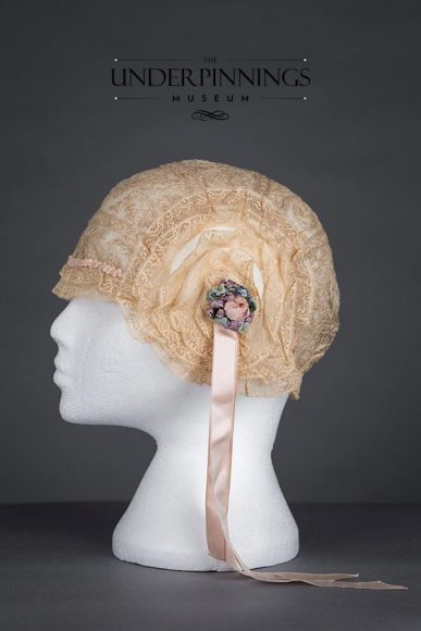 Embroidery and lace boudoir cap with rosettes and silk ribbon streamers. Estimated to be from the 1920s. From The Underpinnings Museum Collection. Photo by Tigz Rice Studios