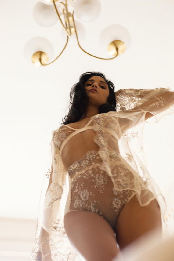 Valentine's Day Lingerie from Anya Lust. Sheer lace embroidered bra, high waist panty, and robe. Model walking down staircase with lighting fixture overhead.