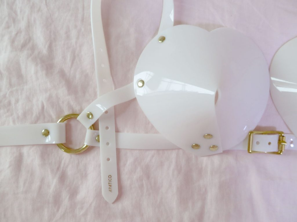 Close up of gold band stamp (reads: Apatico in gold) on Apatico white, PVC  bullet bra halter strap.