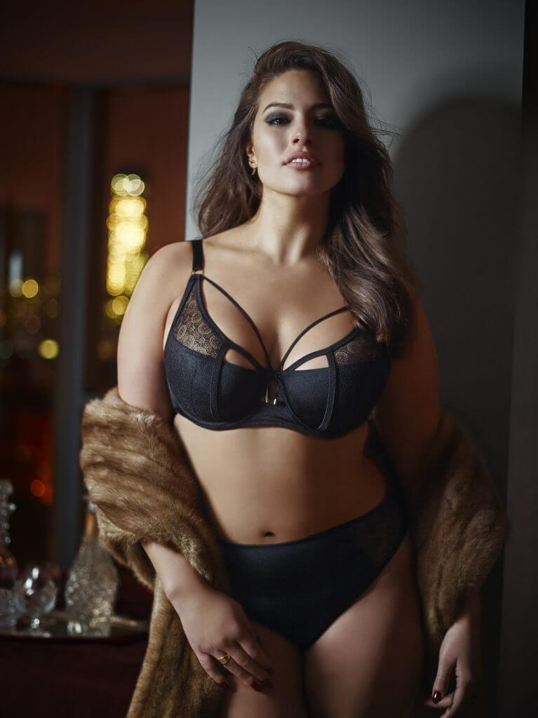 Ashley Graham for Addition Elle. Lingerie Trends - Plus Size. Supermodel in strappy demi cup bra with plain briefs and faux fur wrap. Boudoir Canadian lingerie brands.
