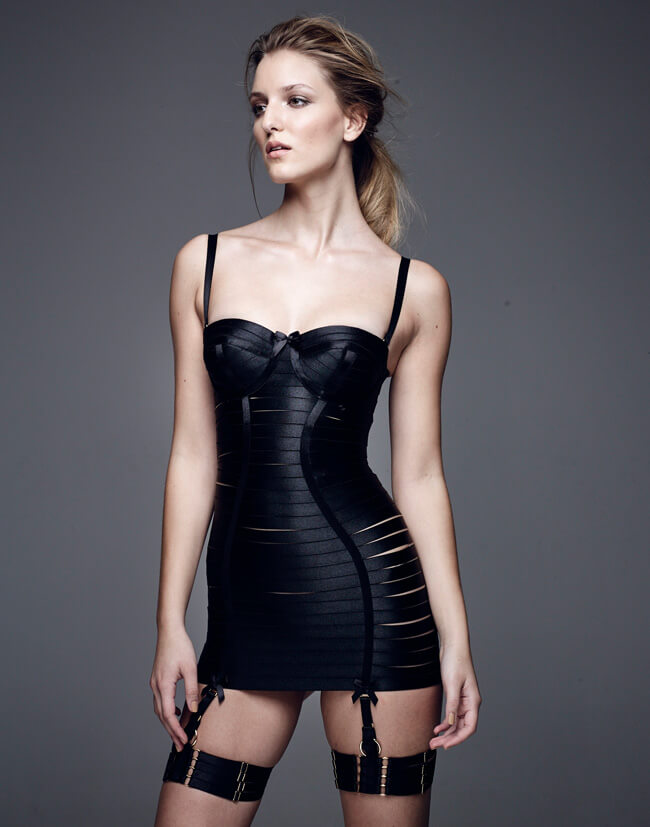 Bordelle. Lingerie Trends - Strappy, Bondage. Black strappy girdle dress or corselette with black leg garters.