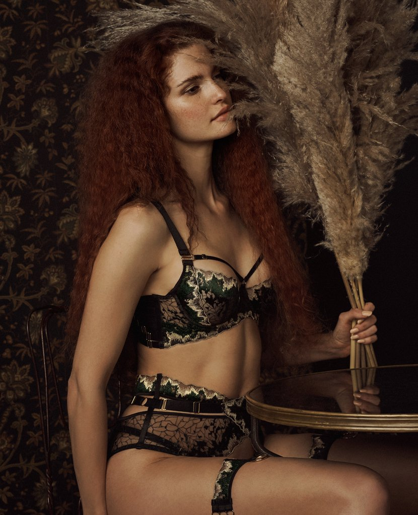 Model wearing Bordelle, expensive lingerie set, black and gold. Strap accents across bra cup, briefs and garter.