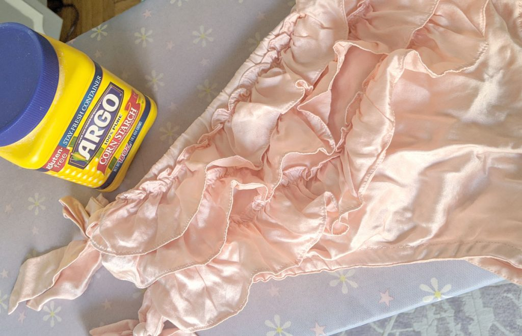 Use cornstarch to remove oil stains from silk lingerie. Photo is of soft pink ruffled silk knickers on an ironing board, with a plastic container of Argo cornstarch next to them.