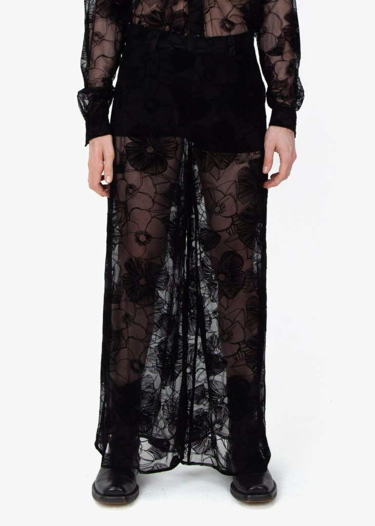Lower front profile, Fomme Gender Neutral Black Lace Pajamas with flower-patterned flocking. Wide leg pants with hidden, side zip closure.