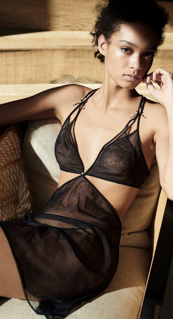 Model sitting, wearing Black, La Perla expensive lingerie set. Sheer slip, bralette, and briefs.