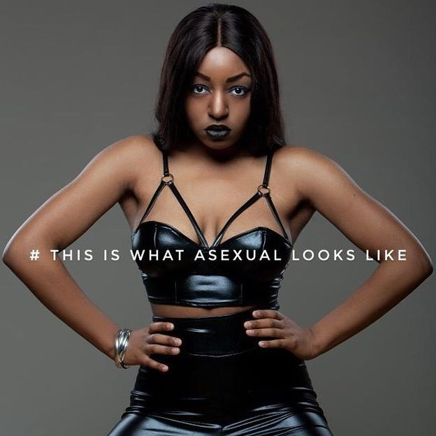 "Yasmin Benoit wearing a black latex look bra and high-waist pants in an ad saying, ""This is what asexual looks like"""
