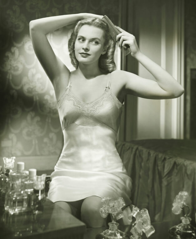 woman in slip brushing hair